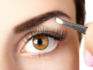 bigstock-Young-woman-plucking-eyebrows-96593342